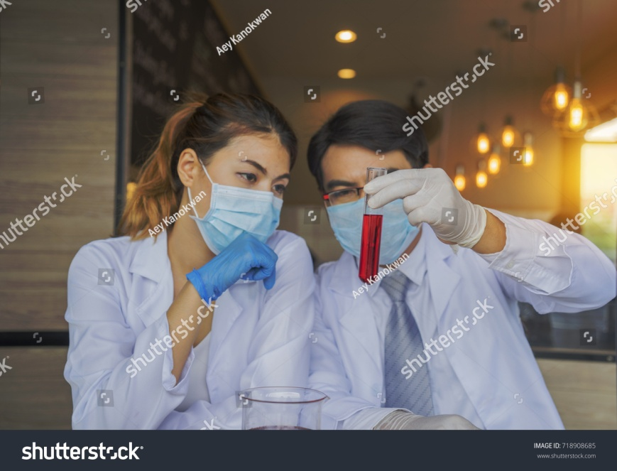 stock-photo-portrait-of-woman-and-man-mask-medical-glove-research-scientist-or-doctor-looking-at-a-test-tube-718908685