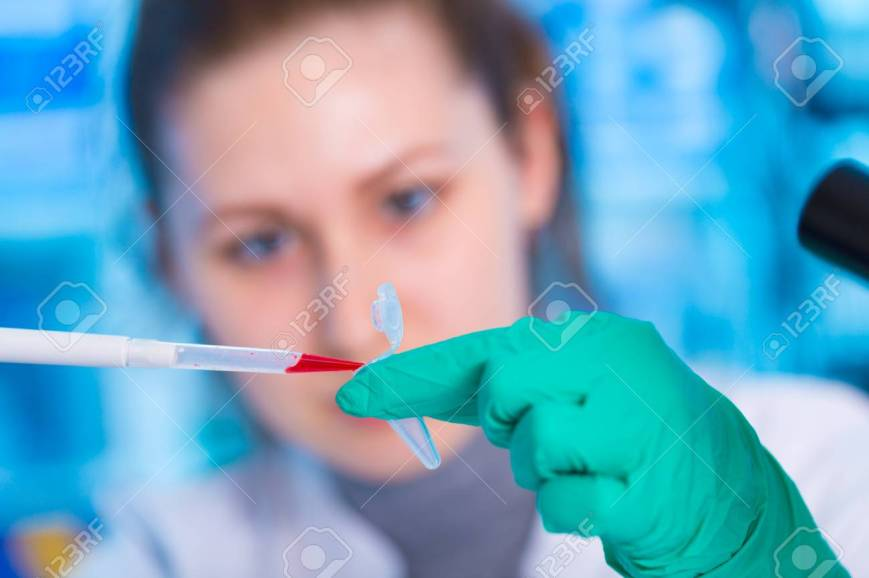 66809334-a-young-chemist-holding-test-tube-with-liquid-during-chemical-experiment-assistant-in-laboratory-wit.jpg
